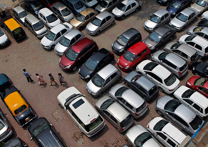 People walk through a car parking lot in New Delhi.