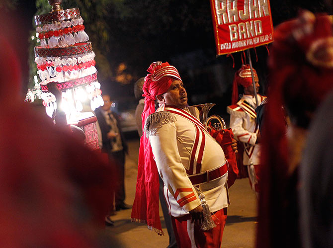 A member of a brass band pauses as his other members perform during a wedding procession in New Delhi.