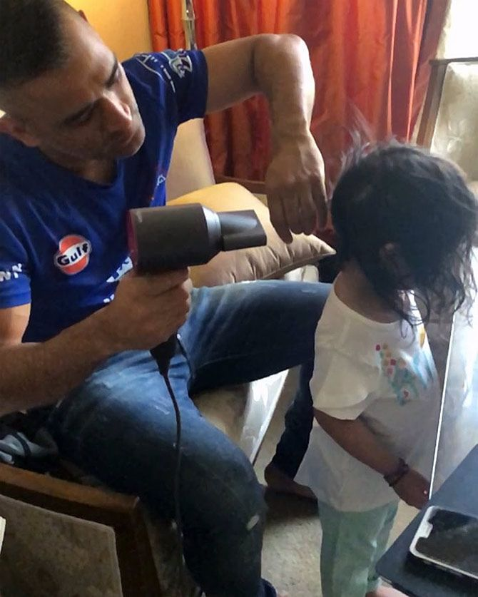 Awww! The cricketer dries his daughter's hair.