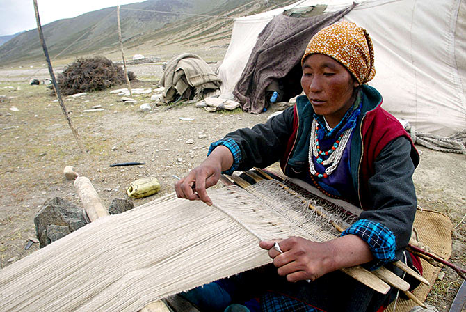 A nomad woman weaves pashmina at Taglang La in Ladakh