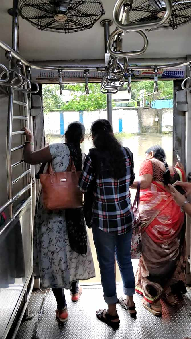 Women passengers peer out of a local train compartment on September 4, 2019. We could see snakes in the water around the tracks. Photographs: Divya Nair/Rediff.com