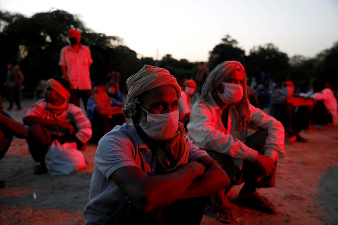 Daily wage workers and homeless people wearing protective masks wait on the banks of Yamuna river as police officers arrange buses to transfer them to a shelter, after India extended a nationwide lockdown. Photograph: Anushree Fadnavis/Reuters.