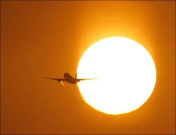 A passenger aircraft is silhouetted against the rising sun during the early morning in New Delhi.