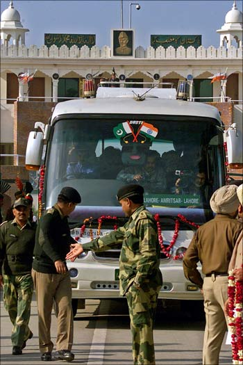 Indian soldiers escort a bus as it crosses over to India from Pakistan at the joint Wagah border-post.
