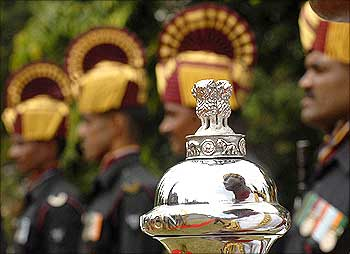 An Indian soldier is reflected on an official emblem of the government of India during Vijay Diwas celebrations in Hyderabad.