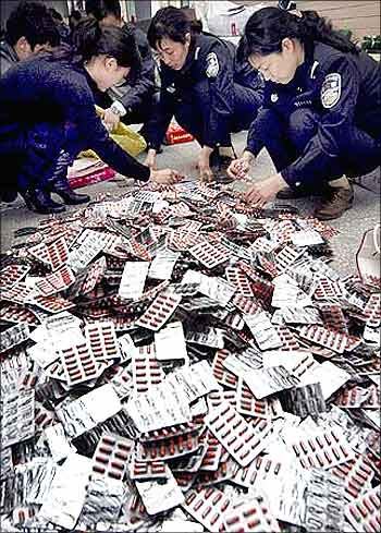 Police check confiscated fake drugs after they smashed a counterfeit gang in Xuchang, Henan province