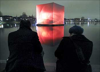 People watch an illuminated so-called CO2 cube pictured in the water of St Jorgens Lake, Copemhagen.