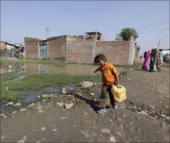 A girl carries water in a slum area next to the Union Carbide Corp pesticide plant in Bhopal.