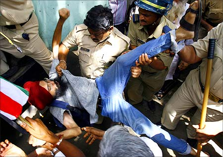 Police forcibly remove a human rights activist from the venue of a demonstration against SEZs near Mumbai.
