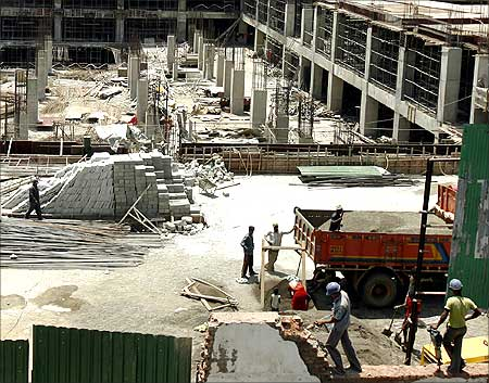 Labourers work at the construction site of a building.