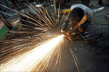 An Indian worker uses an angle grinder.
