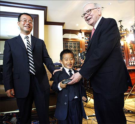 Hedge fund manager Zhao Danyang (L) and his son Zhao Ziyang with Warren Buffett after placing the winning bid in a charity auction in New York on June 24, 2009.Buffett handed his wallet to the younger Zhao and then whispered him a stock tip as they passed by photographers after completing television interviews at New York's famous steak house, Smith & Wollensky.