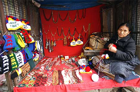 A Buddhist woman wraps wool inside her shop selling ornaments and caps in Mcleodgunj.