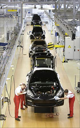 Workers inspect a Panamera car.