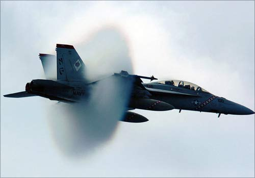 Water vapour builds up around a US Navy F/A-18F Super Hornet as it breaks the sound barrier during a fly-by. The Super Hornet engines are powered by GE.