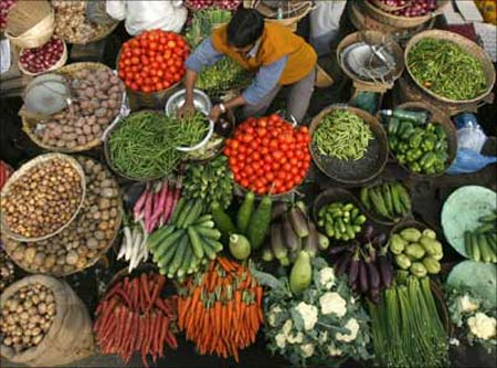 A vendor arranges vegetables at a market in Siliguri.