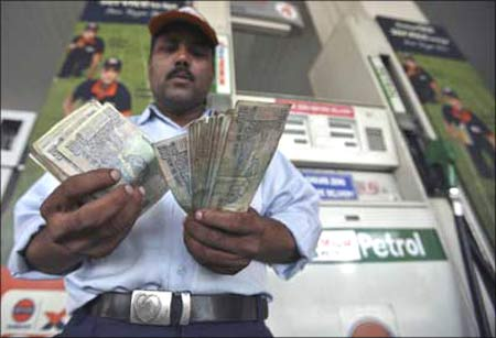 A worker at a gas station counts currency notes.