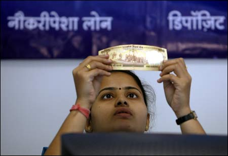 A bank employee checks a Rs 500 note at a counter of Yes Bank's microfinance division in Mumbai.