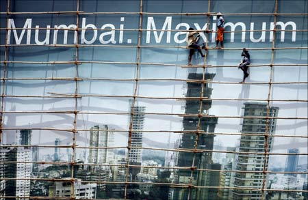 Labourers work on a billboard in Mumbai.