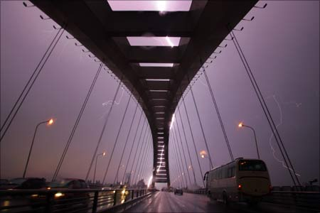 A lightning bolt illuminates the sky above Lupu Bridge during an electrical storm in Shanghai.