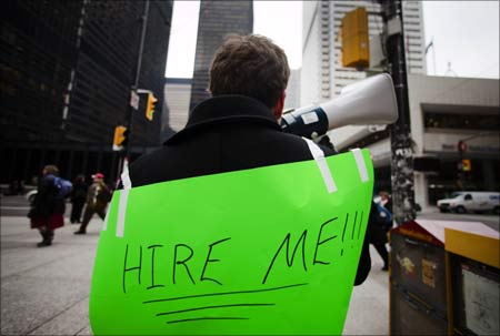 A man, with a sign strapped to his back, uses a megaphone to attract the attention of potential employers.