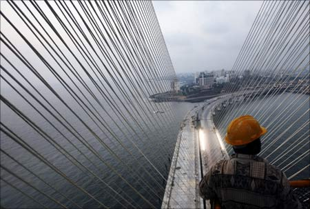 A worker stands on top of a tower at the construction site of the Bandra-Worli sea link in Mumbai.