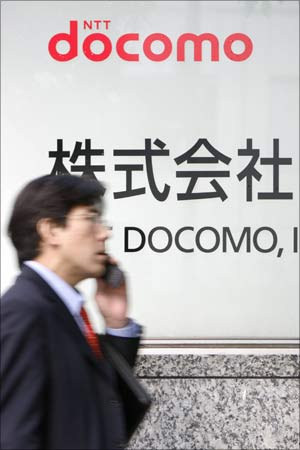A man walks past a signboard of Japan's biggest mobile phone operator NTT Docomo Inc.