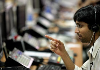 A stock broker monitors indices during trading hours at a brokerage firm in Mumbai.