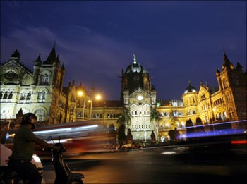 A scooterist stops in front of Chhatrapati Shivaji Terminus railway station in Mumbai.