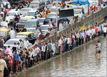 People walk home as traffic after came to a standstill following heavy rains on July 26, 2005, in Mumbai.