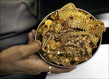 A trader holds gold jewellery at a shop in Mumbai.