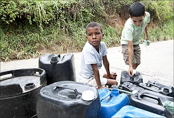 Children wait after filling containers with water at Antimano in Caracas, Venezuela.