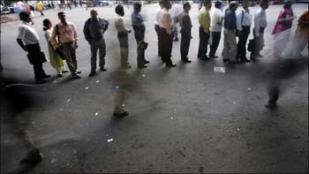 Office-goers stand in a queue in Mumbai.