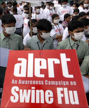 Schoolchildren hold a banner as they take part in a swine flu awareness run in Hyderabad.