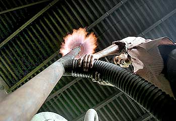 An Indian worker adjust gas pipeline inside a biomass gasifier power plant in Gosaba.