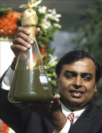 Mukesh Ambani, chairman of Reliance Industries, holds a jar containing the first crude oil produced from their company's KG-D6 block in the country's east coast.