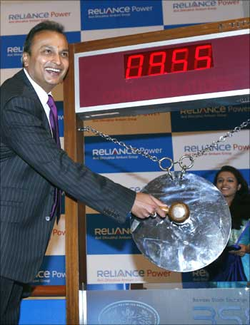 Anil Ambani, chairman of Anil Dhirubai Ambani group, strikes a gong as other officials watch during the listing ceremony of Reliance Power at the Bombay Stock Exchange in Mumbai February 11, 2008.