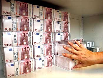 A bank clerk places a pack of 10 Euro notes valuing 10,000 Euros.
