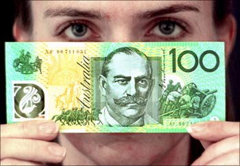 A Reserve Bank of Australia employee holds up the new A$100 note in Sydney.