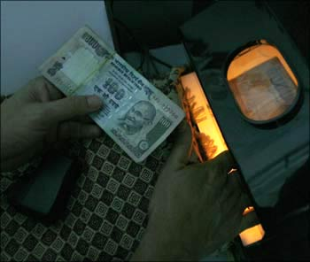 A teller checking a currency note.