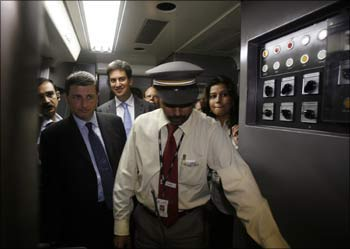 Britain's International Development Minister Douglas Alexander (2nd from left) and Energy and Climate Change Minister Ed Miliband (3rd left) walk inside the driver's cabin of the Delhi Metro Rail Corporation in New Delhi.