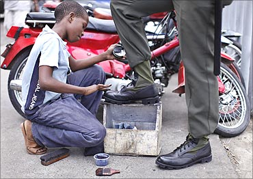 A child polishes military boots in a street in Santo Domingo.