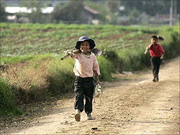 Children carry their tools as they leave the field at the end of the day in Tecpan, Guatemala.