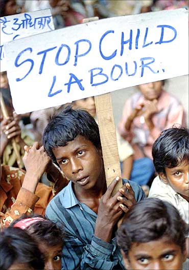 Radhaysham, 13, an Indian child labourer carries a placard during a rally.