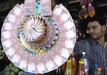 A Kashmiri shopkeeper displays a garland made of Indian currency notes at a market in Srinagar.