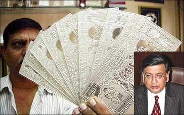 A jeweller displays silver plates in the form of Indian rupee notes. Sunil Mitra (inset).