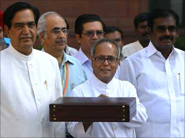 Finance Minister Pranab Mukherjee (C) smiles as he leaves his office to present the 2009/10 Union Budget in New Delhi.
