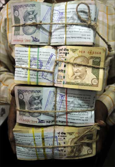 An employee carries bundles of Indian currency notes inside a bank in Agartala, capital of Tripura.