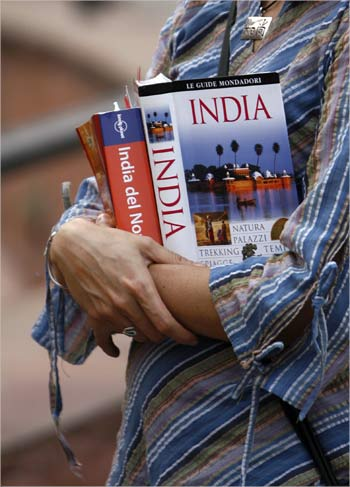 A tourist holds tourist guide books as she visits the Red Fort in the old quarters of Delhi.