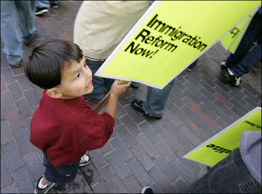A child holds up a placard at a rally organised by protesting immigrants.